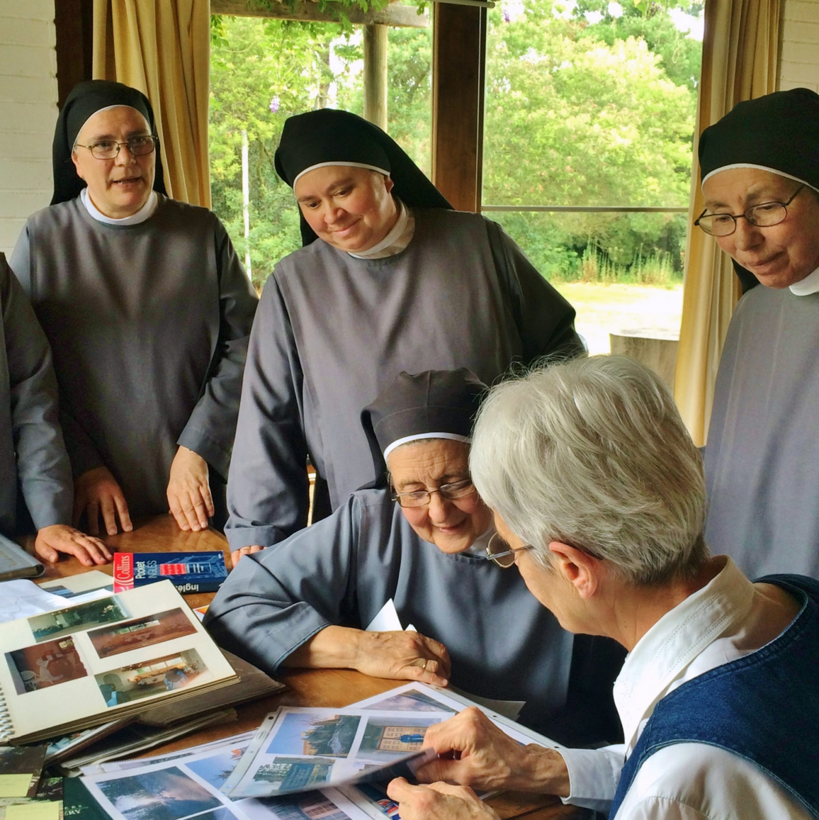 On a visit to Monasterio Santa Maria de Rautén, Sister Theresa Spinler and the Chilean Sisters share photograph albums.